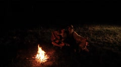 Young Couple Sitting By The Fire In The Evening And Playing On The Guitar Stock Footage