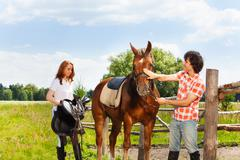 Happy equestrians preparing their horse for riding Stock Photos