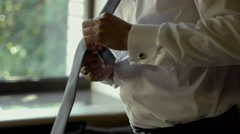 Man in white shirt tying a tie near the window Stock Footage