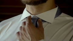 Man in white shirt tying a tie near the window. Stock Footage