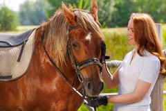 Happy young woman feeding her beautiful bay horse Stock Photos