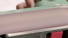 Process of grinding the wooden piece on the belt sander, close-up Stock Footage