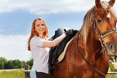 Beautiful smiling woman saddling a horse Stock Photos