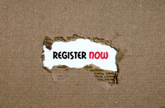 The word register now appearing behind torn paper Stock Photos