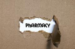 The word pharmacy appearing behind torn paper Stock Photos