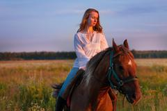 Beautiful horseback rider in a field at sunset Stock Photos