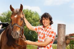 Happy man holding his beautiful horse by a bridle Stock Photos