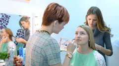 Make-up artist and stylist doing makeup model for photography Stock Footage