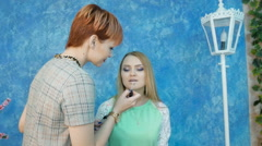 Professional makeup artist applies makeup to a beautiful model, rouge Stock Footage