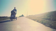 Tracking shot of mother jogging with baby stroller sun flare 4k Stock Footage