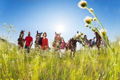 Five equestrians with horses in blossoming meadow Stock Photos