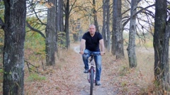 Man cyclist to riding a bicycle in the autumn forest Stock Footage