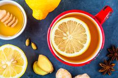 Cup of tea with ginger, lemon, honey, anise and cardamom Stock Photos
