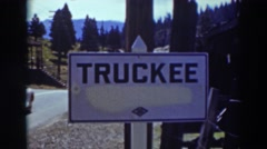 1937: a sign that reads truckee has a vehicle drive down the road past it Stock Footage
