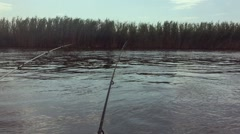 Fishing on the river in the first person, 2 fishing rods, reeds and blue sky. Stock Footage