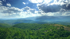 Aerial motion beautiful landscape mountains green forest clouds dramatic sky Stock Footage