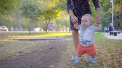 The child makes the first steps, mother help him. Autumn park Stock Footage