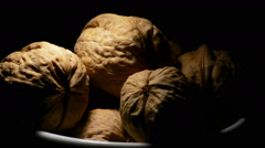 Walnuts nuts in a white bowl gyrating on black background with a cenital light Stock Footage