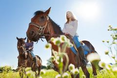 Two active young women training riding horses Stock Photos