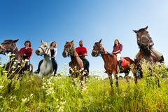 Portrait of happy equestrians riding their horses Stock Photos