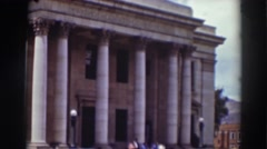 1937: row of columns stand in in front of gray stone building  Stock Footage