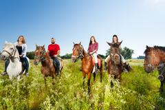 Happy equestrians riding horses in summer field Stock Photos