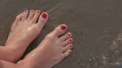 Red manicured female caucasian girl legs through moving sand of sea beach bank Stock Footage