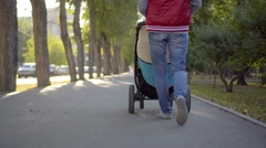 Mother walking with a pram in the park. Autumn nature background. Bottom view Stock Footage