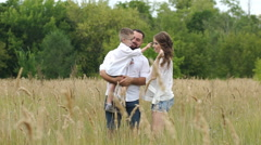 Happy family walking outdoor. Parents hold child on hands and rejoice Stock Footage