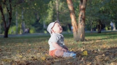 Baby in the forest. Falling autumn leaves. Slow Motion 100 fps Stock Footage