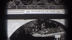 1938: drivers traverse under a bridge marking bonneville dam. BONNEVILLE Stock Footage