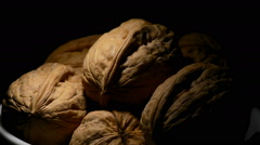 Walnuts in a white bowl gyrating on black background with a cenital light Stock Footage