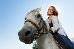 Portrait of happy young woman riding white horse Stock Photos