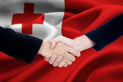 Business people in front of Tonga flag Stock Photos