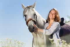 Smiling pretty woman with beautiful white horse Stock Photos