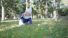 Baby crawling on the grass in the park and eats leaves Stock Footage