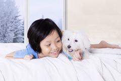 Little girl and canine lying in the bed Stock Photos