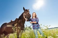 Happy woman with brown stallion in countryside Stock Photos