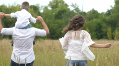 Happy family with child run and have fun in the field Stock Footage