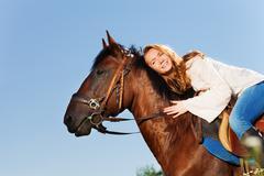 Smiling woman hugging beautiful bay horse Stock Photos