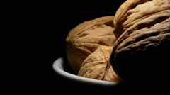 Walnuts nuts in a bowl at right of screen in rotation on black background Stock Footage
