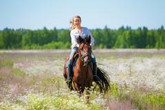 Young woman galloping horseback in flowery meadow Stock Photos