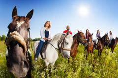 Group of equestrians riding their horses in field Stock Photos