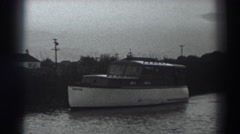 1938: boat traveling down a river past a few houses FORT ROSS CALIFORNIA Stock Footage