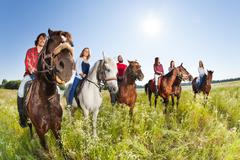 Happy equestrians riding horses in summer meadow Stock Photos