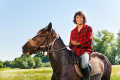 Portrait of happy equestrian riding his horse Stock Photos