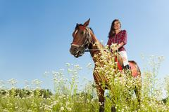 Young woman riding a horse in flowery meadow Stock Photos