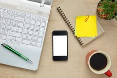 Top view accessories office desk the mobile phone,note paper,coffee,laptop. Stock Photos