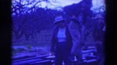 1937: man and family drill holes in boards for farm. SACRAMENTO CALIFORNIA Stock Footage