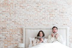 Cheerless depressed couple suffering from influenza together Stock Photos